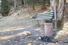 Poubelle en parc avec un banc, des déchets et un charbon de bois images stock