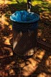 Poubelle publique en métal avec un sachet en plastique bleu photographie stock