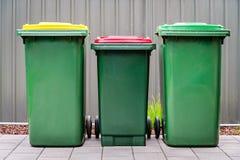 Poubelles à la maison australiennes de wheelie de déchets réglées sur l'arrière-cour images stock