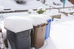 Poubelles d'ordures couvertes dans la neige images stock