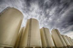 Poubelles de grain contre le ciel menaçant Images stock