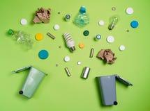 Poubelles et déchets assortis d'isolement sur le vert image stock