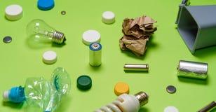 Poubelles et déchets assortis d'isolement sur le vert photo stock