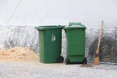 Poubelles vertes de poubelle de déchets de poubelle en dehors de route de fond de mur photographie stock libre de droits