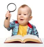 Pouca brincadeira com livro e magnifier Fotografia de Stock Royalty Free