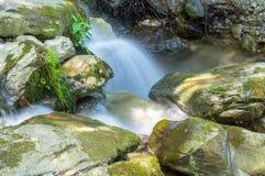 Pouca cachoeira cercada por rochas enormes Foto de Stock