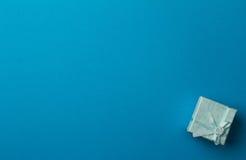 Pouca caixa de presente na luz - fundo azul com copyspace Fotos de Stock