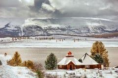 Pouca casa no fundo nevado das montanhas fotos de stock royalty free
