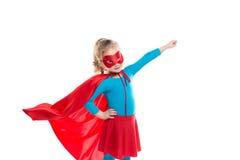 Pouca criança do super-herói do poder (menina) em uma capa de chuva vermelha