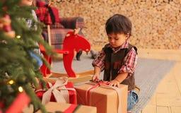 Pouca criança está desembalando presentes fotografia de stock