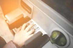 Pouca criança, criança que incorpora números de PIN na máquina do banco do ATM Conceito de pagamentos em linha dos adolescentes i fotos de stock