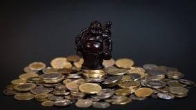 Pouca estátua de Budha em uma pilha das moedas Fotografia de Stock Royalty Free