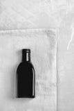 Pouca garrafa preta coloca em um pano cinzento Fotos de Stock Royalty Free