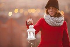 Pouca lanterna com posse mágica da iluminação por uma mulher em um vermelho Imagem de Stock Royalty Free