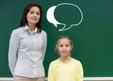 Pouca menina da escola com o professor no quadro-negro Foto de Stock Royalty Free