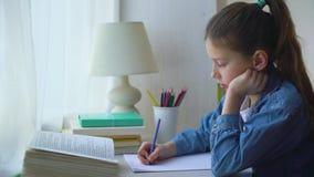 Pouca menina da escola no revestimento das calças de brim que faz somas na folha de papel em casa video estoque