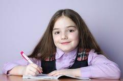 Pouca menina da escola que faz trabalhos de casa na mesa Imagem de Stock Royalty Free
