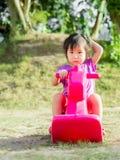 Pouca menina do asain senta-se no cavalo de balanço Imagens de Stock Royalty Free