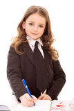 Pouca menina do negócio escreve no bloco de notas Fotografia de Stock Royalty Free