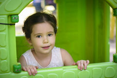 Pouca menina marrom do cabelo que sorri através da janela do teatro das crianças Foto de Stock Royalty Free