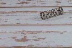 Pouca mola metálica espiral na tabela de madeira branca Fotos de Stock Royalty Free