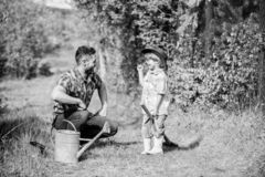 Pouca ruptura Dia da Terra feliz ?rvore geneal?gica que nursering pai e filho no chap?u de vaqueiro no rancho lata molhando, pote fotos de stock