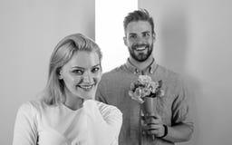 Pouca surpresa para ela O noivo traz flores do ramalhete para surpreend?-la Homem pronto para a data perfeita Gostos machos a fotografia de stock royalty free