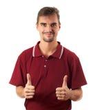 Pouce de jeune homme haut et sourire d'isolement sur le blanc Images stock