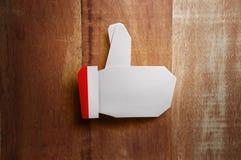 Pouce de Noël d'origami vers le haut du métier de papier sur le fond en bois Images stock