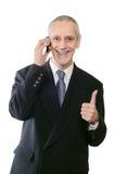 Pouce de sourire vers le haut d'homme d'affaires au téléphone Photographie stock libre de droits