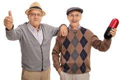 Pouce donnant supérieur avec un autre aîné tenant la grande pilule Photographie stock libre de droits