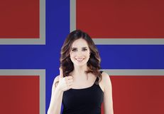 Pouce gai d'apparence de femme de brune sur le fond de drapeau de la Norvège Vivant, travail, éducation et stage en Norvège images libres de droits