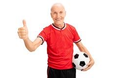 Pouce se tenant supérieur du football et de donner  Photo stock