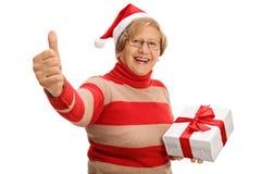 Pouce se tenant supérieur gai de cadeau de Noël et de donner  Photographie stock libre de droits