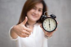 Pouces avec une horloge pendant le bon temps ou le bon travail de finition sur le concept de temps Image libre de droits
