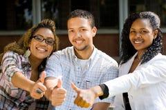 Pouces d'étudiants universitaires vers le haut Photographie stock libre de droits