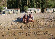 Pouces de couples vers le haut à la plage de sable Images stock