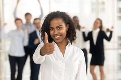 Pouces de représentation femelles africains satisfaisants vers le haut des employés heureux à l'arrière-plan image libre de droits