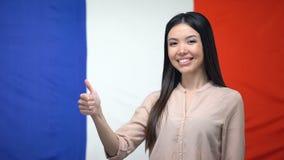 Pouces- de représentation femelles asiatiques heureux sur le fond français de drapeau, calibre banque de vidéos