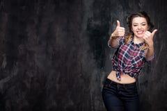 Pouces de signe d'exposition de fille bons dans la chemise à carreaux et des jeans sur le fond gris-foncé photos libres de droits