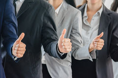 Pouces ginving d'homme d'affaires et d'équipe de femme  Images stock