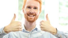 Pouces par les deux mains, homme rouge positif réussi de barbe de cheveux Photo stock