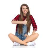 Pouces se reposants de sourire de femme  Image stock