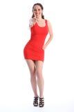 Pouces vers le haut par le femme sexy de sourire dans la robe rouge courte Photos stock