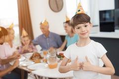Pouces vers le haut Un garçon posant dans la perspective d'une famille qui s'est réunie à une table de fête Images stock