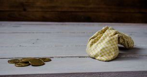 Pouch of gold coins on wooden background stock photo