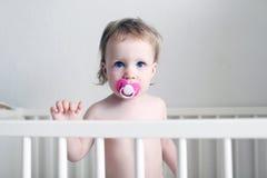 Pouco 1 ano de bebê com o manequim na cama branca Imagens de Stock Royalty Free
