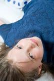 Pouco 8 anos de menina idosa que encontra-se no assoalho Foto de Stock