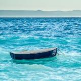 Pouco barco azul seesawing em ondas Imagens de Stock