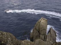 Pouco barco com turbilhão da hélice com nas rochas do primeiro plano foto de stock royalty free